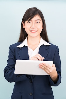 Asian teenage girl in suit using computer digital tablet isolate on blue background