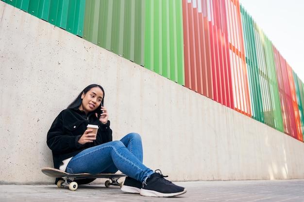 콘크리트 벽에 기대어 스케이트보드에 앉아 야외에서 전화 통화를 하는 아시아 10대 소녀