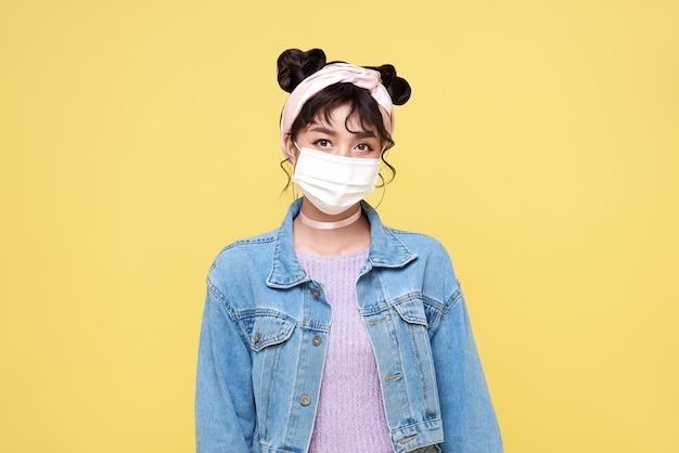 노란색 배경에 고립 된 바이러스 covid-19로부터 그녀를 보호하기 위해 마스크를 쓰고 아시아 십 대 소녀.