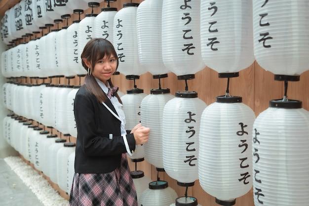アジアの10代の少女アジアの民族の日本の制服を着て立っている