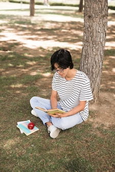 Asian teenage student reading book under tree