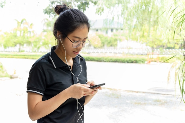 Asian teenage  with glasses listening music on cell phone.