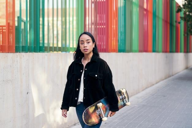 스케이트보드를 손에 들고 거리를 걷고 있는 아시아 10대 여성