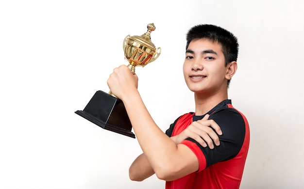 Asian teenager football player holding trophy with celebrate pose.