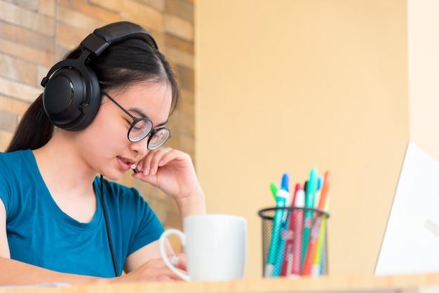 헤드셋 안경을 쓴 아시아 10대 여학생은 집에서 학교 원격 교육 수업에서 랩톱 컴퓨터 온라인 학습을 사용하여 노트북에 메모를 작성합니다.