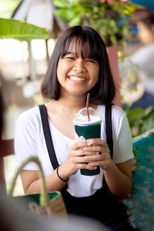 手に冷たい飲み物のボトルとアジアの10代の幸せ顔