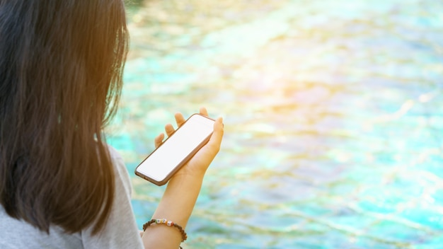 Asian teenager holding mobile phone beside swimming pool , thailand