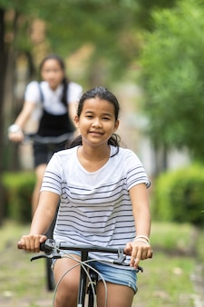 Asian teenager riding a bicycle in green public park