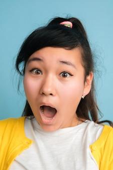青いスタジオで隔離のアジアのティーンエイジャーのクローズアップの肖像画