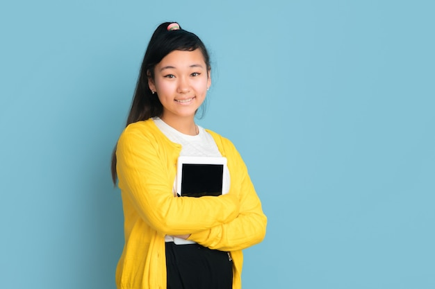 Asian teenager's portrait isolated on blue studio background. beautiful female brunette model with long hair. concept of human emotions, facial expression, sales, ad. holding tablet, smiling.