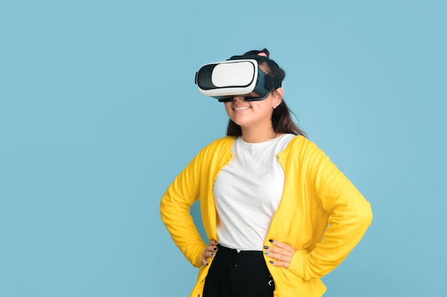 Asian teenager's portrait isolated on blue studio background. beautiful female brunette model with long hair. concept of human emotions, facial expression, sales, ad. playing with vr-glasses, headset.