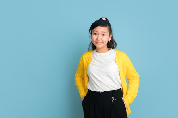 Asian teenager's portrait isolated on blue studio background. beautiful female brunette model with long hair. concept of human emotions, facial expression, sales, ad. posing, looks confident.