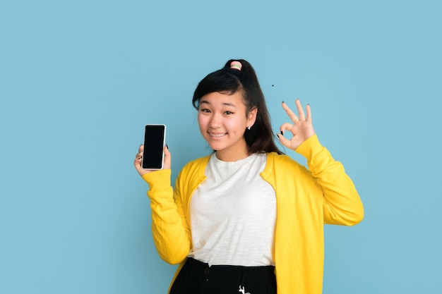 Asian teenager's portrait isolated on blue studio background. beautiful female brunette model with long hair. concept of human emotions, facial expression, sales, ad. showing blank phone screen.