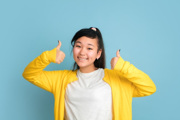 Asian teenager's portrait isolated on blue studio background. beautiful female brunette model with long hair. concept of human emotions, facial expression, sales, ad. smiling, thumbs up, pointing.