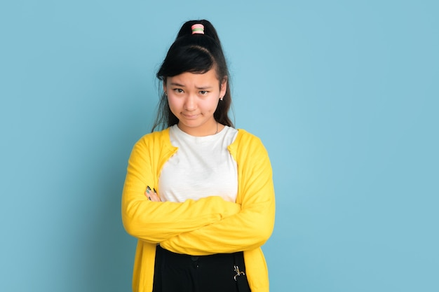 Asian teenager's portrait isolated on blue studio background