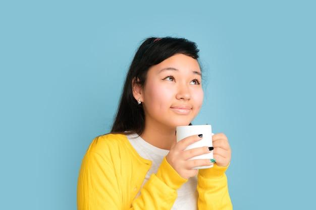 青いスタジオの背景に分離されたアジアのティーンエイジャーの肖像画。長い髪の美しい女性ブルネットモデル。人間の感情、顔の表情、販売、広告の概念。コーヒーやお茶を飲む。