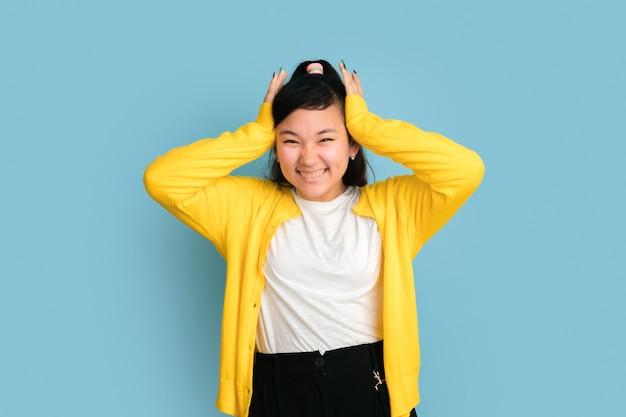 블루 스튜디오 배경에 고립 된 아시아 십 대의 초상화. 긴 머리를 가진 아름 다운 여성 갈색 머리 모델입니다. 인간의 감정, 표정, 판매, 광고의 개념. 웃음, 머리를 손에 들고.
