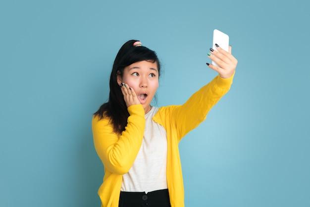 블루 스튜디오 배경에 고립 된 아시아 십 대의 초상화. 긴 머리를 가진 아름 다운 여성 갈색 머리 모델입니다. 인간의 감정, 표정, 판매, 광고의 개념. 셀카 또는 동영상 블로그 만들기.