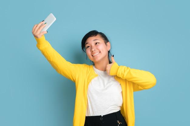 青いスタジオの背景に分離されたアジアのティーンエイジャーの肖像画。長い髪の美しい女性ブルネットモデル。人間の感情、顔の表情、販売、広告の概念。自撮り写真やブログを作る。