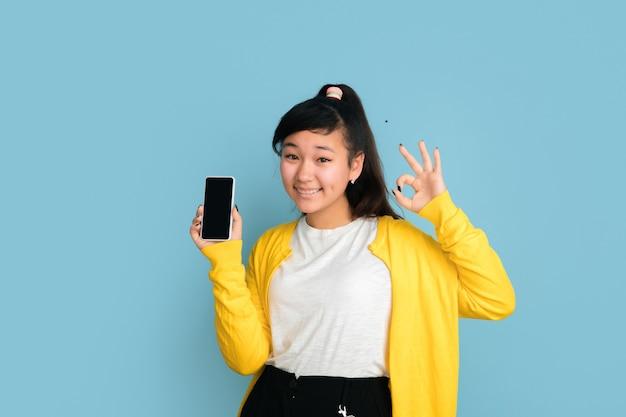 블루 스튜디오 배경에 고립 된 아시아 십 대의 초상화. 긴 머리를 가진 아름 다운 여성 갈색 머리 모델입니다. 인간의 감정, 표정, 판매, 광고의 개념. 빈 전화 화면을 표시합니다.