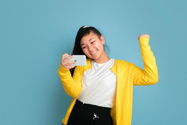 블루 스튜디오 배경에 고립 된 아시아 십 대의 초상화. 긴 머리를 가진 아름 다운 여성 갈색 머리 모델입니다. 인간의 감정, 표정, 판매, 광고의 개념. 전화를 사용하여 웃고, 행복한 승리.