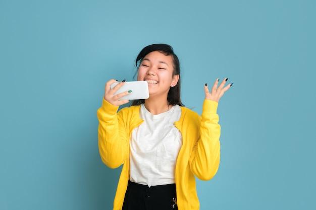 青いスタジオの背景に分離されたアジアのティーンエイジャーの肖像画。長い髪の美しい女性ブルネットモデル。人間の感情、顔の表情、販売、広告の概念。電話を使って、笑顔で、幸せな勝利。