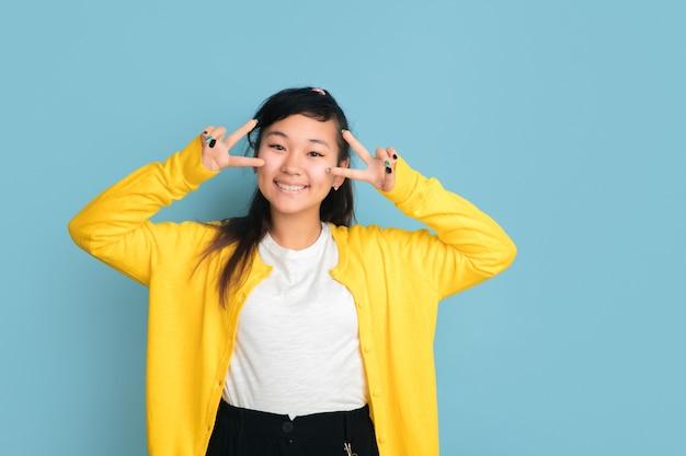 青いスタジオの背景に分離されたアジアのティーンエイジャーの肖像画。カジュアルなスタイルの長い髪の美しい女性ブルネットモデル。人間の感情、顔の表情、販売、広告の概念。かわいいポーズ。