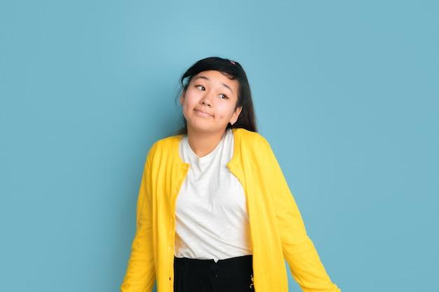 青いスタジオの背景に分離されたアジアのティーンエイジャーの肖像画。カジュアルなスタイルの長い髪の美しい女性ブルネットモデル。人間の感情、顔の表情、販売、広告の概念。不確かに。
