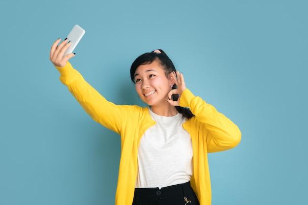 Портрет азиатского подростка, изолированные на синем фоне студии