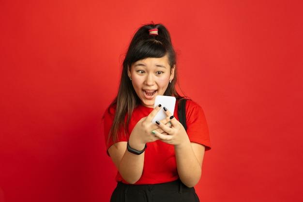 빨간색 공간에 고립 된 아시아 십 대의 초상화. 캐주얼 스타일에 긴 머리를 가진 아름 다운 여성 갈색 머리 모델