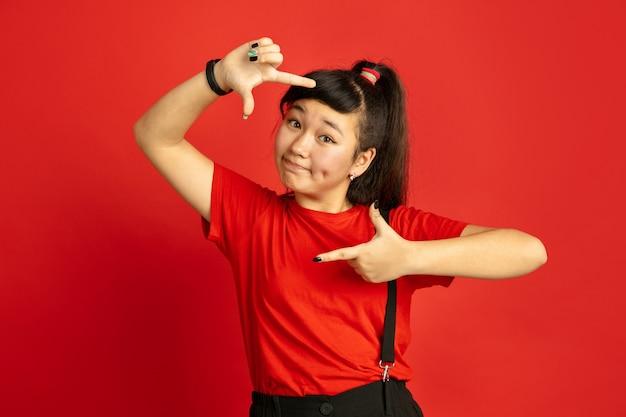 Портрет азиатского подростка изолирован на красном пространстве