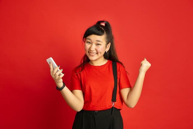 빨간 스튜디오 배경에 고립 된 아시아 십 대의 초상화. 캐주얼 스타일에 아름 다운 여성 갈색 머리 모델입니다. 인간의 감정, 표정, 판매, 광고의 개념. 행복, 스마트 폰 들고.