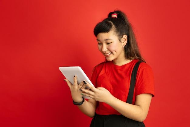 빨간 스튜디오 배경에 고립 된 아시아 십 대의 초상화. 캐주얼 스타일에 긴 머리를 가진 아름 다운 여성 갈색 머리 모델. 인간의 감정, 표정, 판매, 광고의 개념. 태블릿을 들고.
