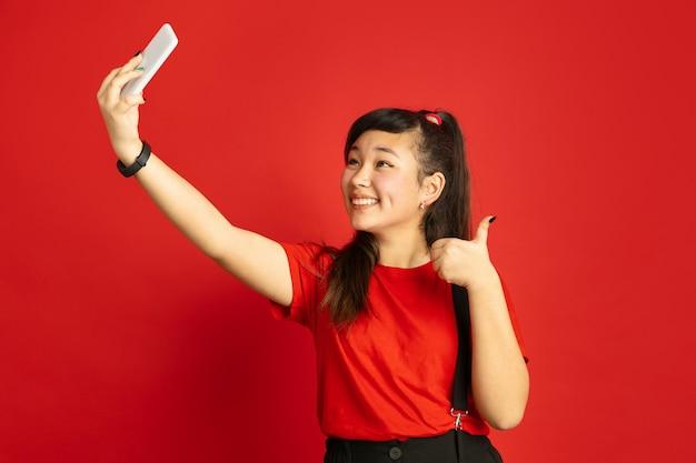 빨간 스튜디오 배경에 고립 된 아시아 십 대의 초상화