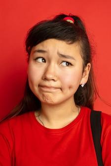 Ritratto dell'adolescente asiatico isolato sullo spazio rosso
