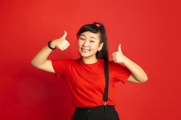Asian teenager's portrait isolated on red  space