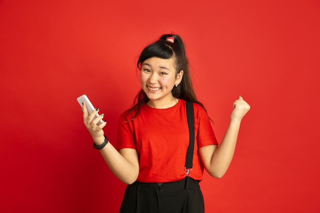 Asian teenager's portrait isolated on red studio background. beautiful female brunette model in casual style. concept of human emotions, facial expression, sales, ad. happy, holding smartphone.