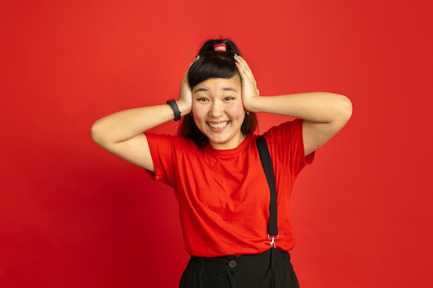 Asian teenager's portrait isolated on red studio background. beautiful female brunette model with long hair in casual. concept of human emotions, facial expression, sales, ad. astonished, shocked.