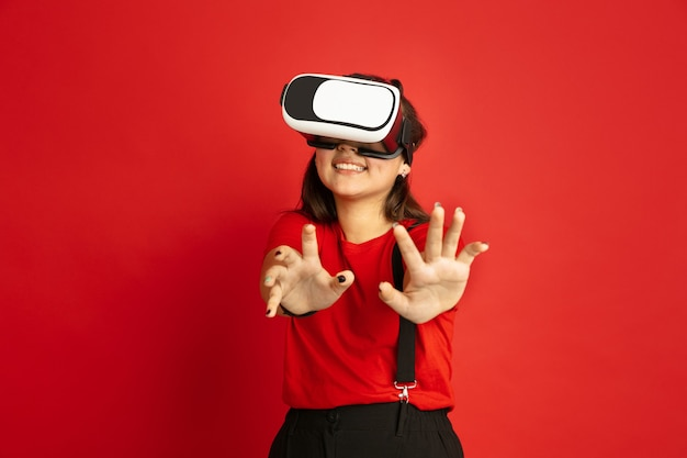 Asian teenager's portrait isolated on red studio background. beautiful female brunette model with long hair in casual style. concept of human emotions, facial expression, sales, ad. plays vr-headset.