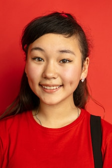 Asian teenager's portrait isolated on red studio background. beautiful female brunette model with long hair in casual style. concept of human emotions, facial expression, sales, ad. smiling cute.