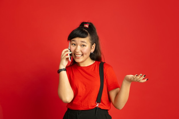 Asian teenager's portrait isolated on red studio background. beautiful female brunette model with long hair in casual style. concept of human emotions, facial expression, sales, ad. talking on phone.