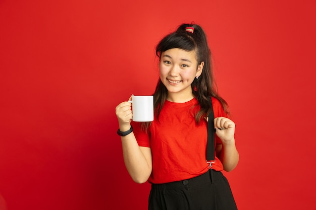 Asian teenager's portrait isolated on red studio background