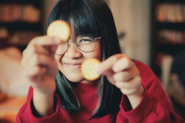 Азиатский подросток показывает кремовый крекер в домашней столовой