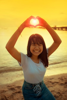 Asian teenager sign heart shape by hand with beautiful sunset sky