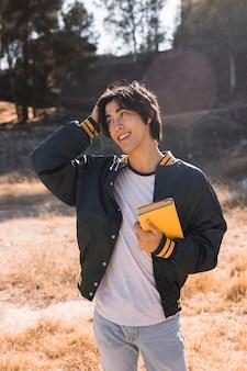 Азиатский подросток, стоя с книгой в парке