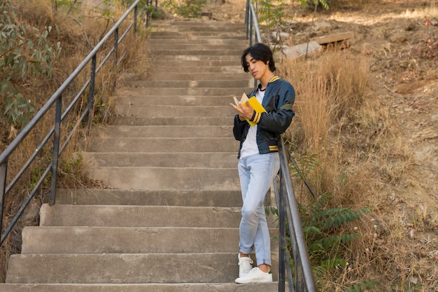 Asian teenager standing with book on stairs