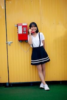 노란색 동기화 벽에 공중 전화의 이전 모델에 얘기하는 아시아 십대