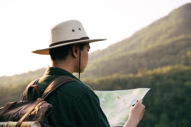 森の中を山の頂上までハイキングするためにpaoerマップとコンパスを使用しているアジアのティーンエイジャー。