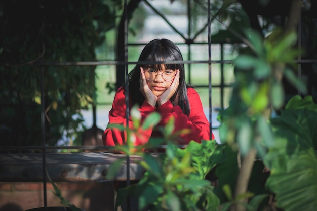 Asian teenager wearing red sweater  sitting  outdoor