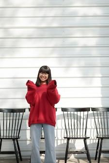 흰 벽에 빨간 스웨터 서 입고 아시아 십 대